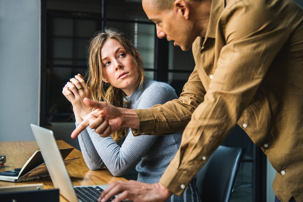 A man and a woman in an office with a laptop. The man is pointing at the laptop and talking to the woman. The woman is looking at him defiantly