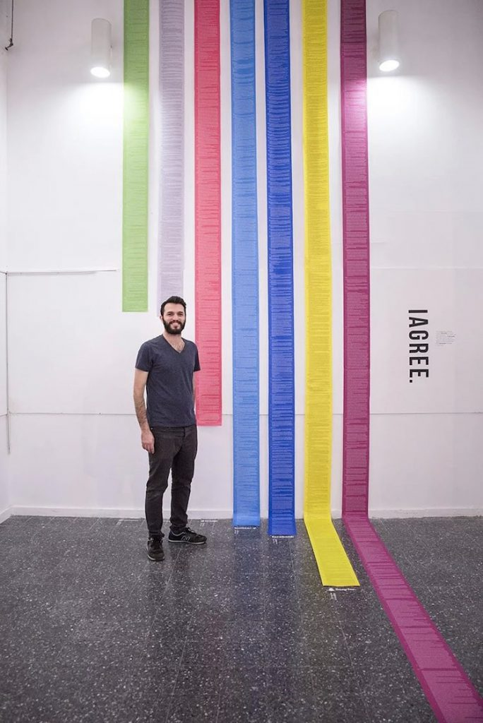 Photo depicts Dima Yarovinsky standing next to seven different colored scrolls of paper, each of varying but very long lengths, and each containing the Terms and Conditions from a separate online service.