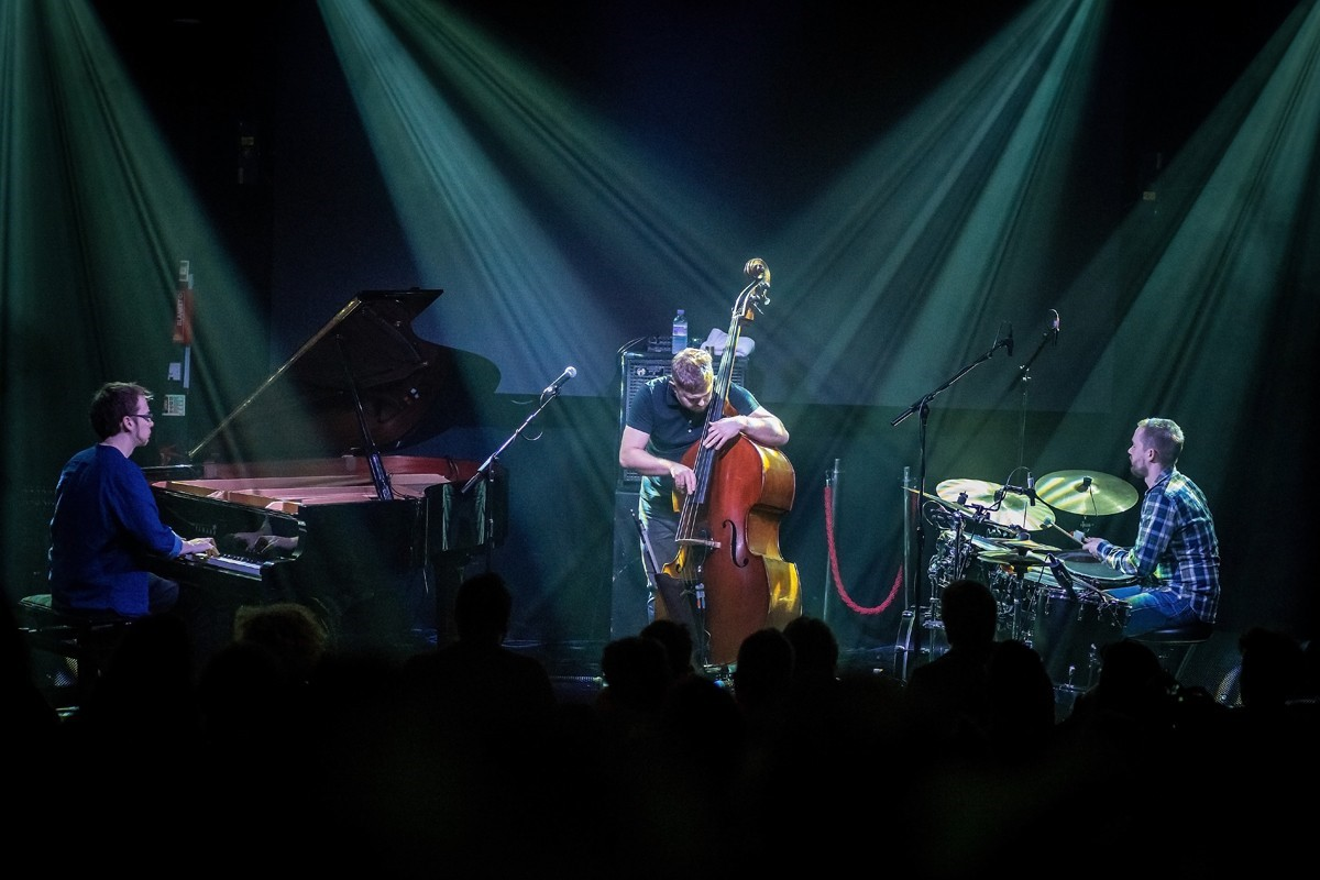 A group of musicians giving a concert on stage, including a piano player, drummer, and stand-up bass.