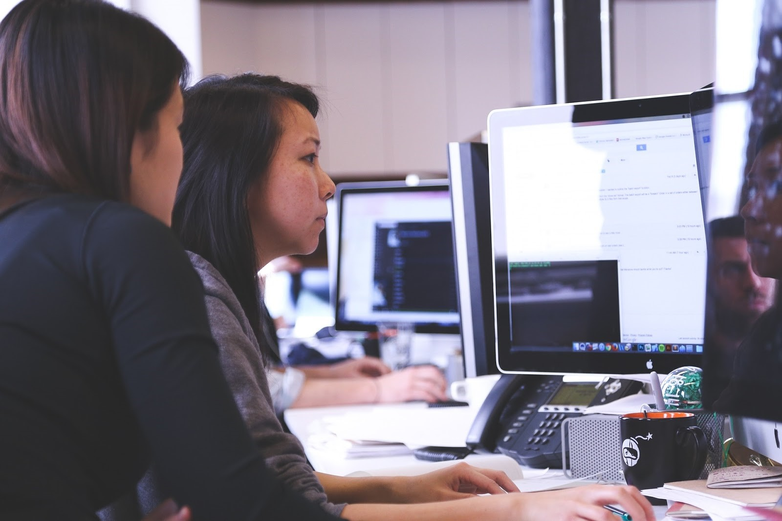 Photo of two people working at a computer.