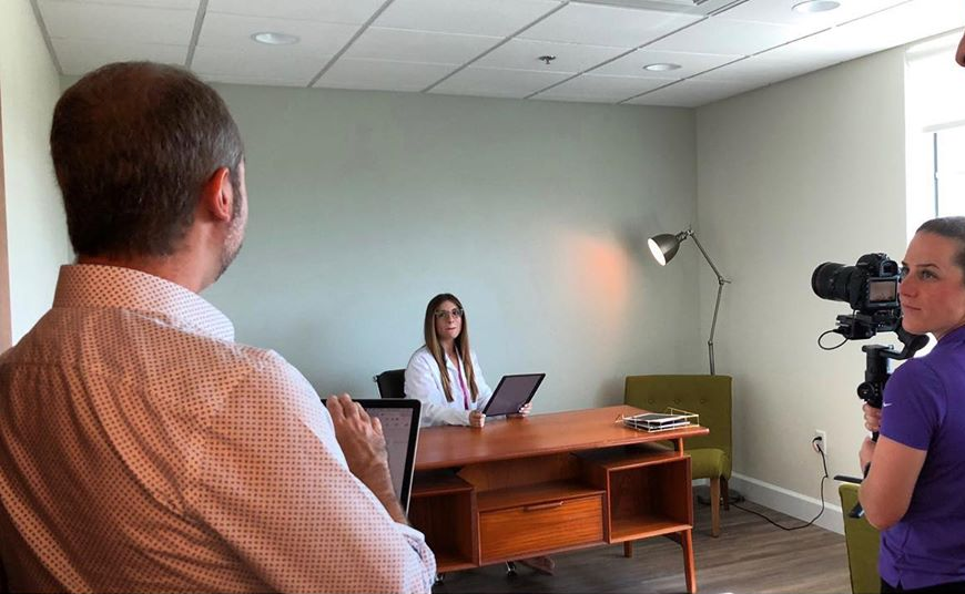 Photo of a person sitting at a desk with another person directing her and a person holding a camera.