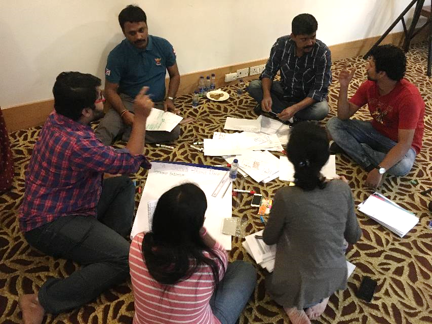 Photo of a group of people sitting in a circle in active discussion.