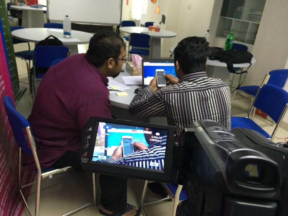 Two people working together while being video recorded.