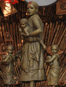 Photo of a sculpture of the goddess standing with her children.