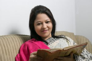 Photo of a seated woman holding an open book and smiling at the camera.